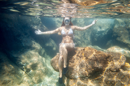 Young woman snorkeling near rocks underwater in the tropical sea