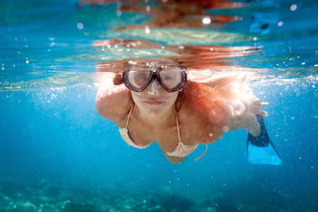 Smiling woman snorkeling in clear water, underwater tropical sea