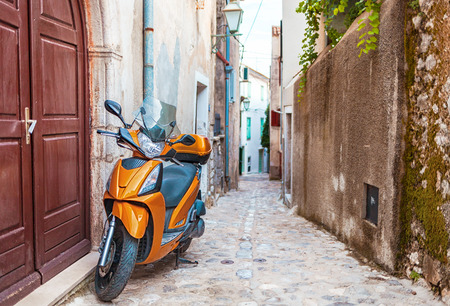 Scooter in narrow street with stone houses, Croatia Stock Photo