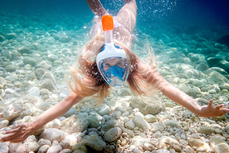 Woman snorkeling with full face mask in the tropical sea Stock Photo