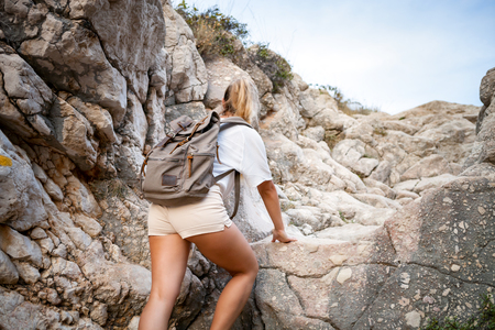 Hiker woman on hiking trail climbing on mountain among rocks, travel and active lifestyle concept