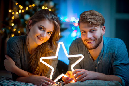 Couple in love at Christmas evening holding glowing white LED star, cozy dark living room 版權商用圖片