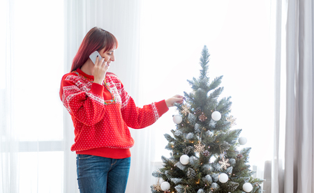 Young woman call mobile phone by Christmas tree