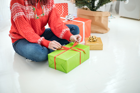 Young woman sitting on white floor near christmas tree preparing gift box