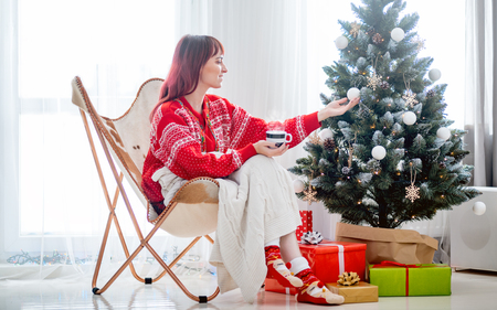 Young woman sitting on armchair by Christmas tree and presents, relax during holiday