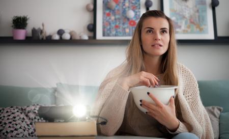 Woman on sofa watching movie using digital LCD video projector, home theater Фото со стока - 114262422