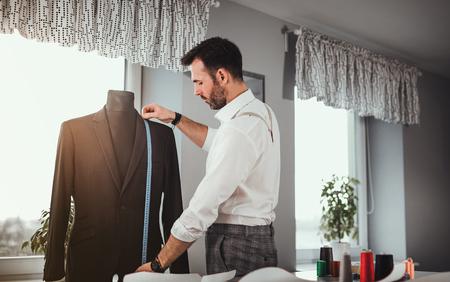 Tailor measuring jacket suit on mannequin at fashion design workshop