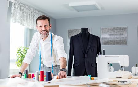 Tailor shop owner over work desk, craftsman in sewing workshop