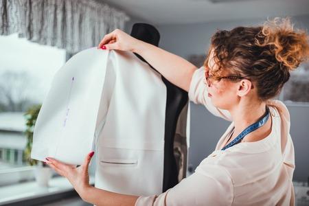 Tailor measuring lady jacket on mannequin at fashion design workshop 写真素材