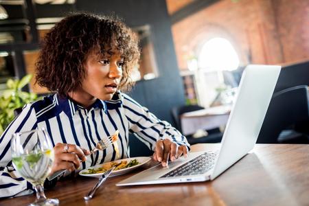 Shocked black female at restaurant using laptop 版權商用圖片