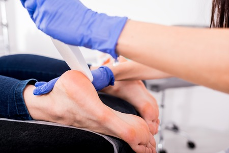 Peeling feet pedicure procedure at cosmetic salon