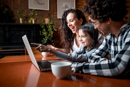 Happy multiethnic family having fun while using laptop together at restaurant