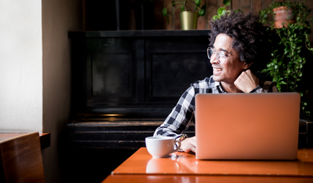 African man in glasses using laptop while sitting at restaurant, concept of young people working