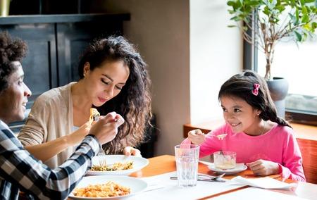 Szczęśliwa afroamerykańska rodzina jedząca razem lunch w restauracji i dobrze się bawiąca