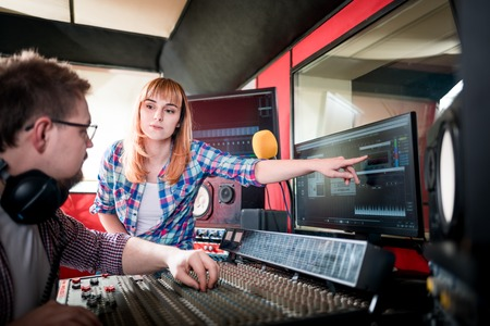 Music engineer and musician working together in recording studio using mixing desk Stock Photo