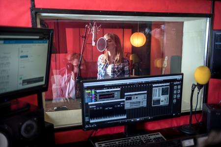 Female singer during vocal recording at music studio Stock Photo