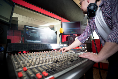 Sound producer working at recording studio using soundboard and monitors Stockfoto