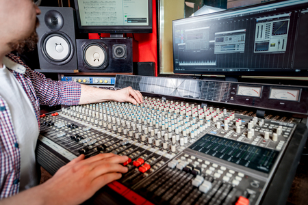 Sound producer working at recording studio using soundboard and monitors Stock Photo