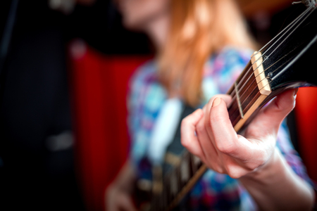 Female singer with electric guitar recording a song in studio