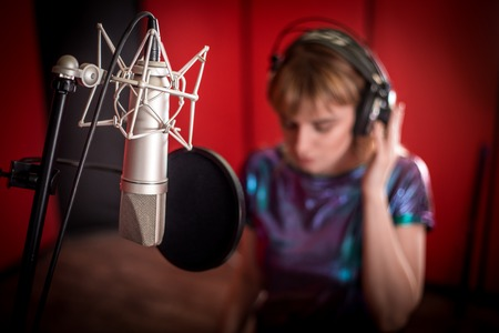 Female singer with microphone recording a song in music studio