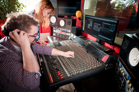 Music producer and musician in recording studio using soundboard for mixing sound