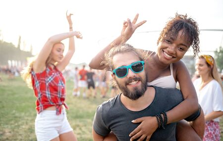 Group of friends having fun at summer music festival