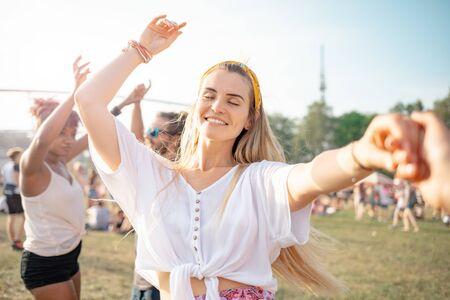 Hermosa joven mujer de pelo largo bailando con amigos al aire libre en el festival de música Foto de archivo