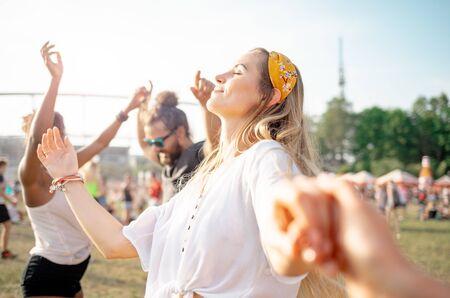 Schöne junge langhaarige Frau tanzt mit Freunden im Freien beim Musikfestival