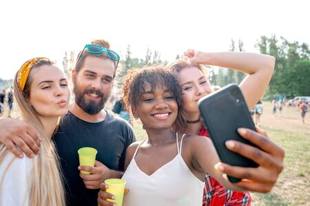 Multiethnic group of young people taking selfie to social media at music festival