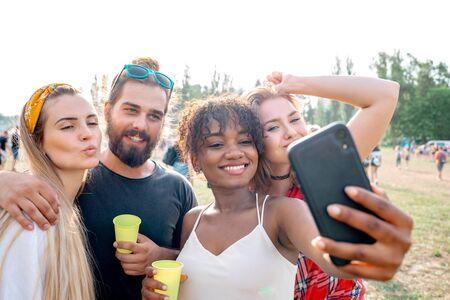 Multiethnische Gruppe junger Leute, die beim Musikfestival Selfie in den sozialen Medien machen