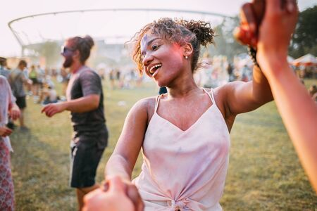 African American young woman with friends dancing at summer holi festival Stock Photo