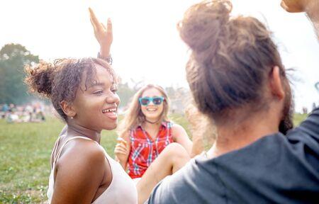 小组朋友坐草和获得乐趣在夏天音乐节