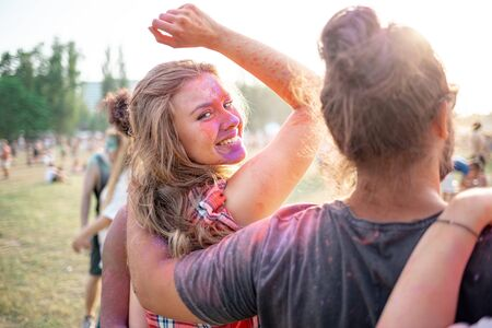Beautiful young woman covered in colorful powder standing with friends at holi festival