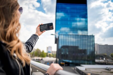 Young smiling woman taking photo by smartphone on the modern city street