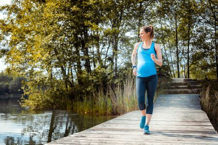 Active pregnant woman running outdoor, sport during pregnancy Reklamní fotografie - 128027035
