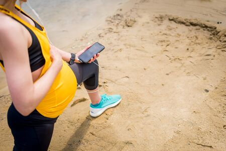 Pregnant woman during fitness exercises outdoor using smartphone with sport app