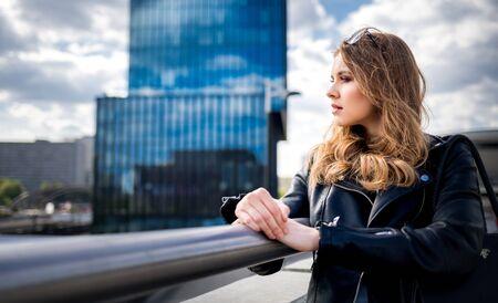 Woman thinking about future among office buildings and modern city Фото со стока