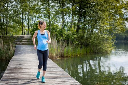 Active pregnant woman running outdoor, sport during pregnancy 写真素材 - 128340792