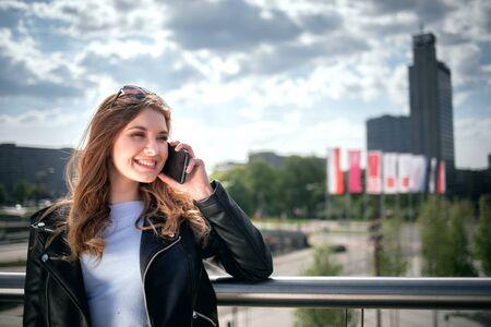 Mujer joven con smarthphone en ciudad moderna Foto de archivo