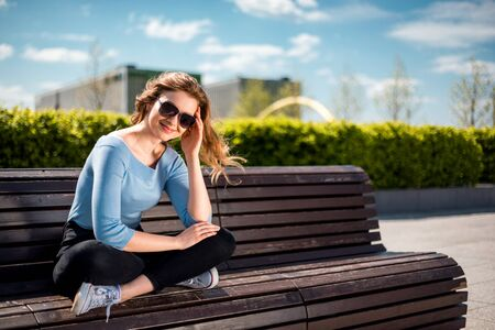 Happy smiling woman sitting on bench in city urban space during summer