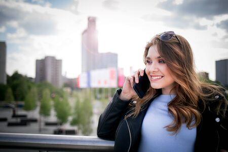 Mujer joven con smarthphone en ciudad moderna