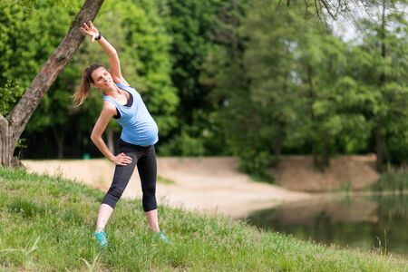 Esercizi di fitness donna incinta all'aperto Archivio Fotografico