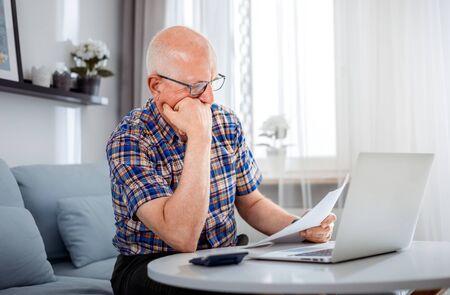 Worried senior male checking bills using laptop at home