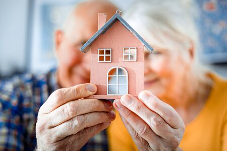 New house concept, happy senior couple holding small home model Standard-Bild