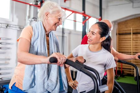 Senior woman biking at the gym with personal trainer