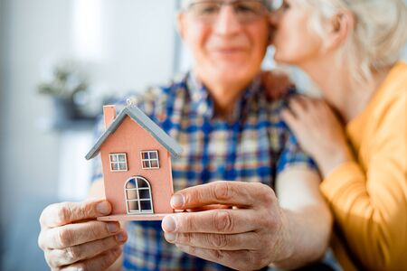 New house concept, happy senior couple holding small home model Stockfoto