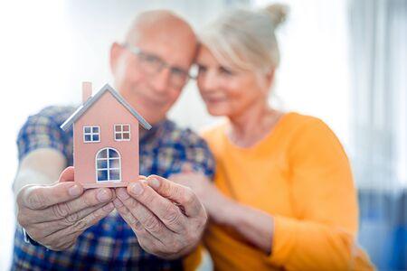 New house concept, happy senior couple holding small home model Banco de Imagens