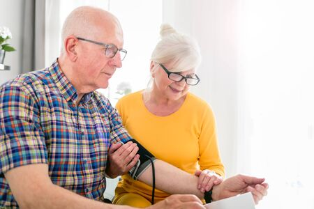 Senior wife doing blood pressure measurement at home to her husband