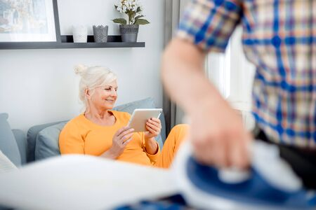 Senior wife using tablet while her husband doing housework with iron and clothes