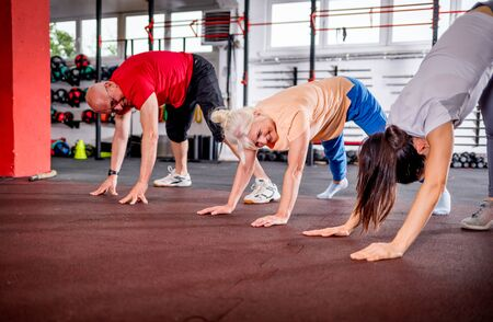 Senior people workout with personal trainer at the gym Reklamní fotografie - 127358257